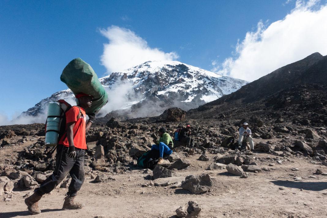 Einheimische Träger mit Kilimanjaro im Hintergrund