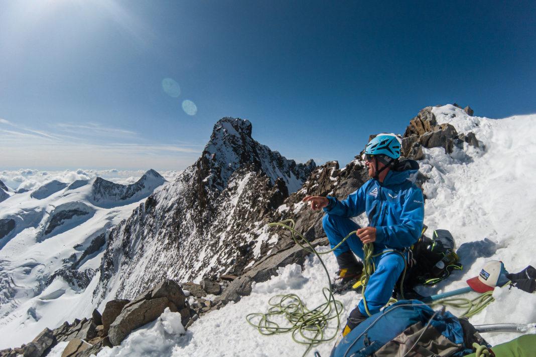 Bergsteiger bei einer Pause am Piz Bianco mit dem Piz Bernina im Hintergrund